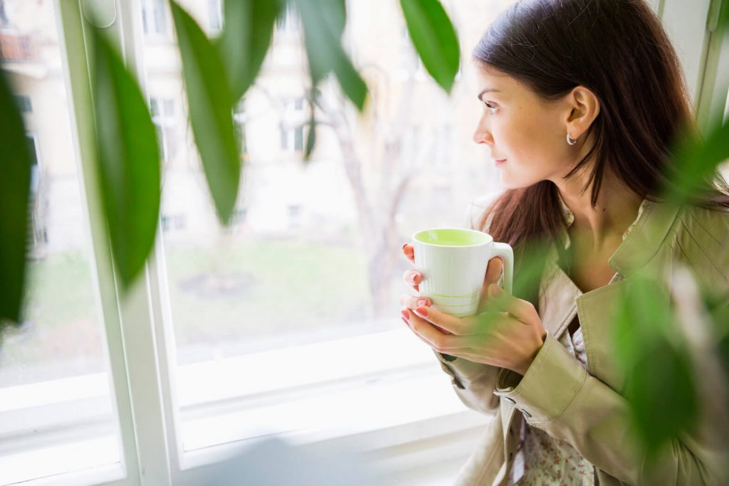 woman with mug staring out window