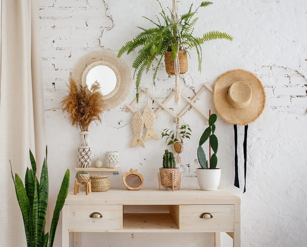 desk with plants and hat on wall