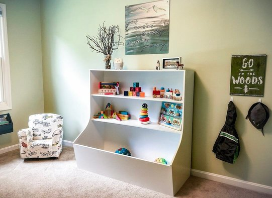Montessori toddler room white bookcase with colorful toys