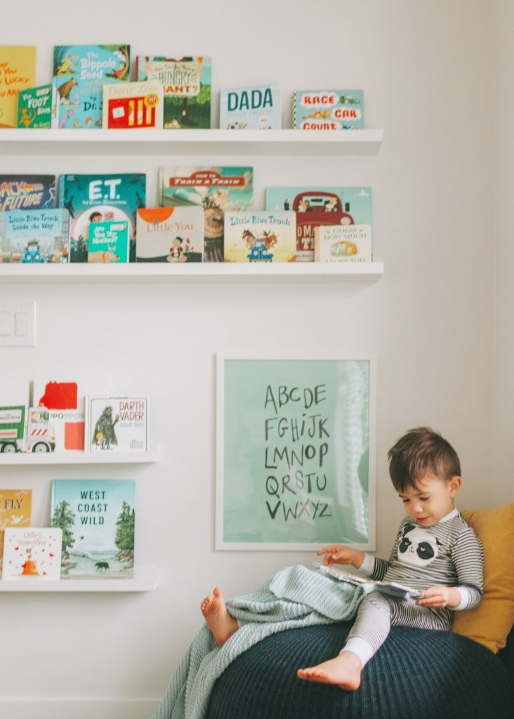 little boy reading on chair with books on shelves