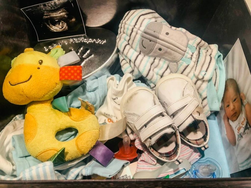 collection of memorable baby items in box